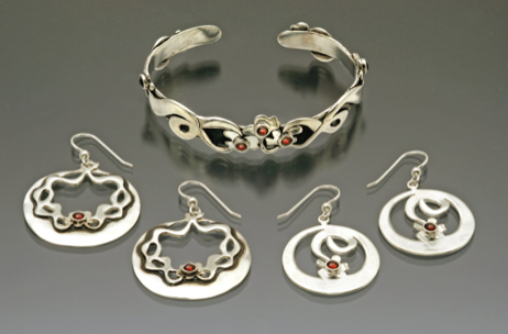 Sterling silver bracelet with vines and 7 flowers(two on either side of the main bunch). Available with garnets or with turquoise stones. Flower and Vine Bracelet with two matching pairs of earrings with flowers and vines.